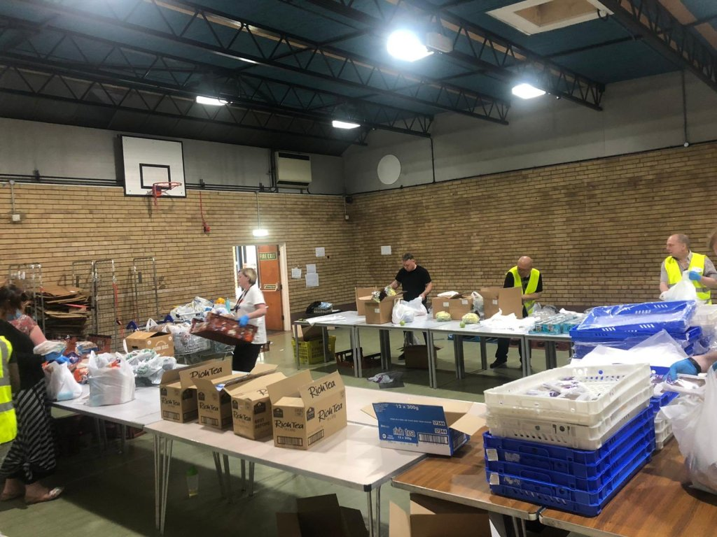 Shows volunteers in high vis jackets around tables packing food parcels