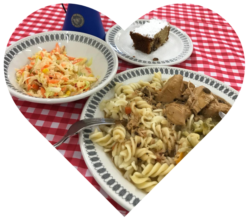 A heart shap showing plates of food on a checked tablecloth