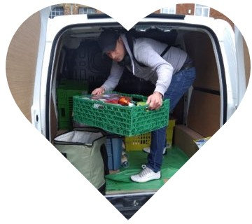 Volunteer taking a crate out of the van