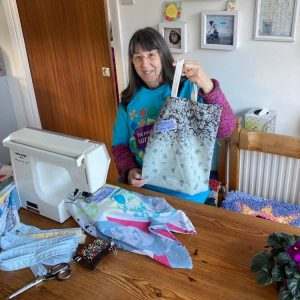 Volunteer wearing a turquiose Incredible Surplus t-shirt, sat at her sewing machine showing us a morsbag she has made.