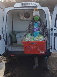 A volunteer in an Incredible Surplus t-shirt, face mask, and bobble hat unloads a crate of lettuces from the new electric refrigerated van.